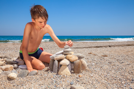 Pebble Beach: Boy building pebble castle on a beach