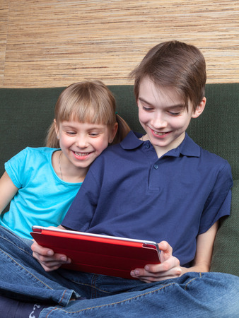 Children wearing casual clothes playing or watching a movie on a touch pad at home sitting on a green sofa. Boy and girl are half-siblings. Brother is holding tablet with red cover. They are looking at screen smiling.