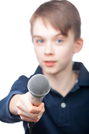 young boys: Boy holding a microphone conducting an interview, focus on microphone face is blurred