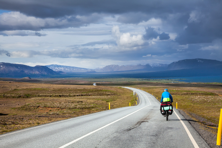 mountain landscape: Cycle tourist on a road in Iceland Stock Photo