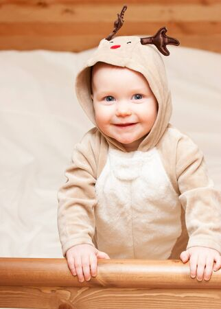 Cute little baby girl wearing christmas deer costume looking at camera smiling photo
