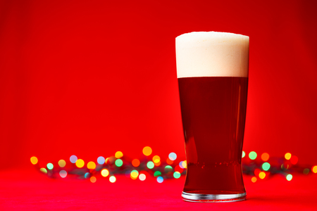 ipa: Full glass of bear or ale with blurred christmas lights in background