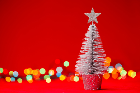 small tabletop christmas tree with blurred christmas lights in background stock photo 48900780