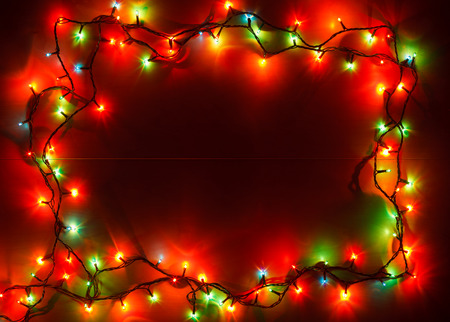 christmas illuminations: Christmas lights of different colors frame on wooden planks Stock Photo
