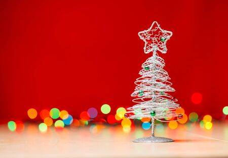 small tabletop christmas tree with blurred christmas lights in background stock photo 48900786