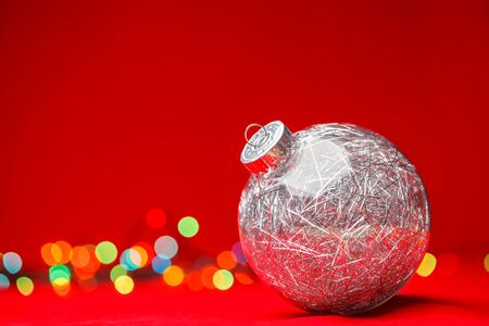 Transparent Christmas bauble filled with silver tinsel on red background with blurred christmas lights