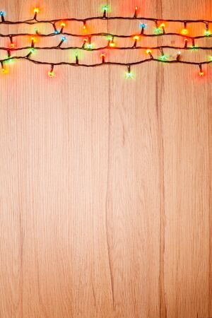 festoon: Christmas lights of different colors on a wooden board