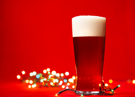 ale: Full glass of bear or ale with christmas lights on red background Stock Photo