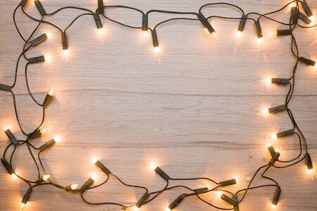 christmas lights background: Christmas lights  frame on a wood Stock Photo