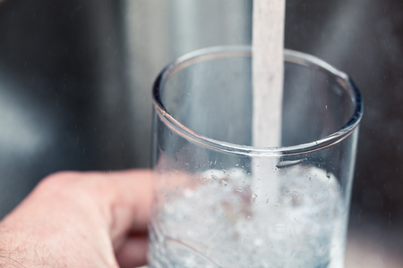 Closeup shot of a man pouring a glass of fresh water from a kitchen faucet Imagens