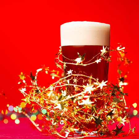 Full glass of bear or ale with tinsel and christmas lights on red background Stock Photo