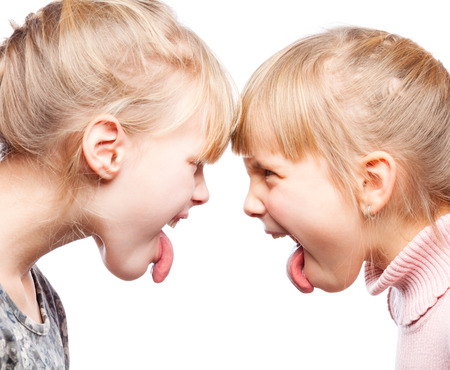 stick children: Two little girls unfriendly stick out tongues teasing each other