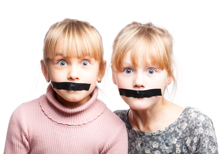 tapes: Portrait of two little girls with duct tape on their mouths - silenced child concept