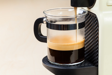 making coffee: Single-serving coffee machine dispenses  espresso in a glass cup Stock Photo