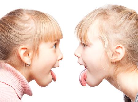 sacar la lengua: Dos ni�as sobresalen lenguas burlas entre s� Foto de archivo