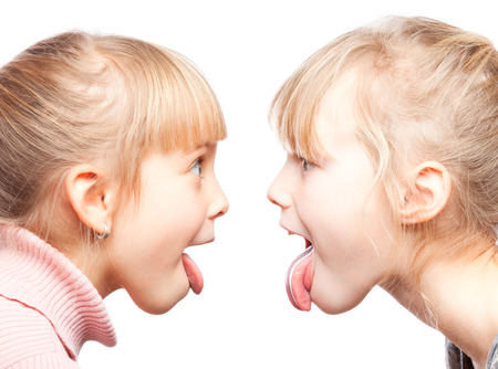 Two little girls stick out tongues teasing each other