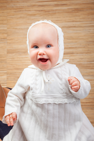 baptize: Cheerful six month baby girl wearing white christening clothes Stock Photo