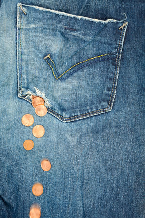 pocket: Coins fall out from a hole in jeans pocket
