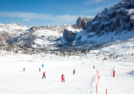 dolomites: Skiers going down the slope at Sella Ronda ski route in Dolomites, Italy Stock Photo