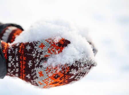 hand woven: Woman wearing knitted woolen  mittens holding fresh snow in cupped hands Stock Photo