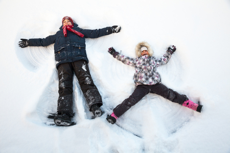 boy lady: Happy boy and girl  having fun together lying in a snow making snow angels