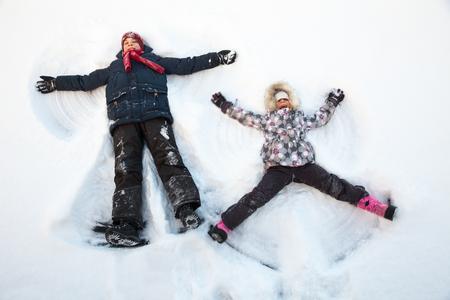 nene y nena: Muchacho y muchacha felices divertirse juntos acostado en una nieve haciendo �ngeles de nieve