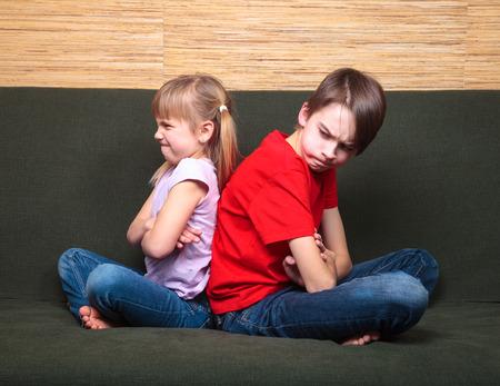conflicto: Hermano y hermana con ropa casual, sentado en un sofá verde en brazos caseros cruzaron espalda con espalda enojados entre sí
