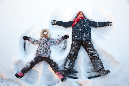 12 13 years: Happy boy and girl  having fun together lying in a snow making snow angels