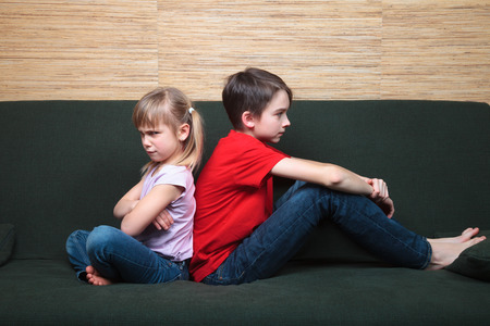 Brother and sister  wearing casual clothes  sitting on a green sofa back to back sad and frown Standard-Bild