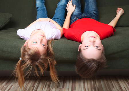 green sofa: Brother and sister  wearing casual clothes  laying upside down on a green sofa at home smiling