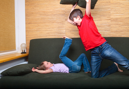sibling rivalry: Brother and sister  wearing casual clothes  playing on a green sofa at home fighting with pillows