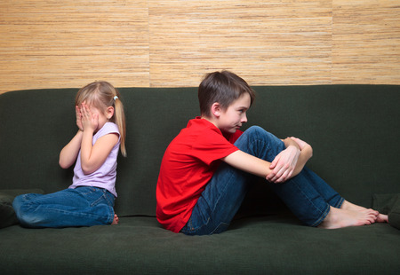 girl home: Brother and sister  wearing casual clothes  sitting on a green couch back to back arter fight. Girl covers her face with hands Stock Photo