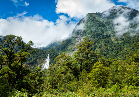 Fiordland National Park at the South Island of New Zealand with temperate rainforest, snow capped steep mountains and a waterfall in background