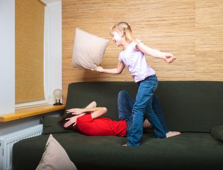 brothers: Brother and sister  wearing casual clothes  playing on a green sofa at home fighting with pillows