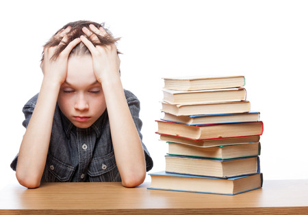 Portrait of frustrated schoolboy sitting at a desk with books holding his head having learnind problems