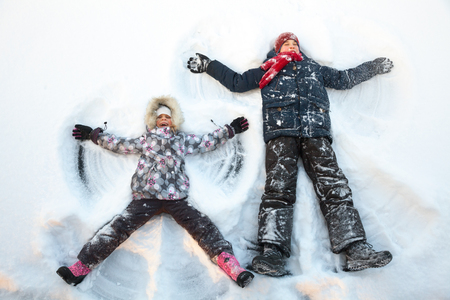 12 13 years: Happy boy and girl  having fun together laying in a snow making snow angels