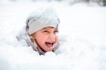 snowbank: Little girl wearing winter clothing having fun laying in a fresh snow Stock Photo