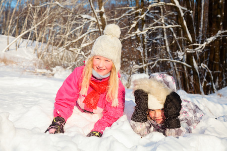 Two little girls wearing winter clothing having fun playing in a fresh snow outdoors photo