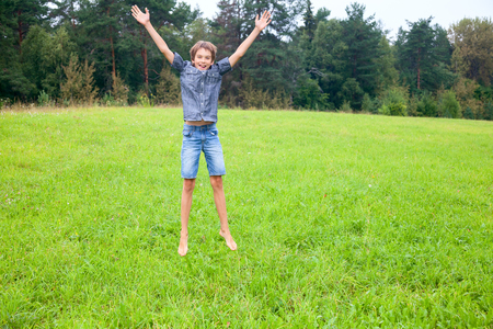 12 13 years: Kid jumping on the meadow in a summer forest