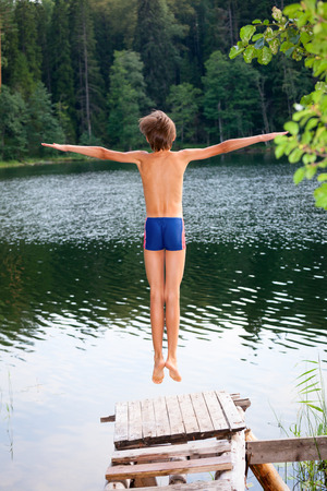 13: Kid jumps off a wooden dock into the water in a summer forest Stock Photo