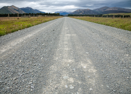 unsurfaced road: Straight gravel road through pasture in New Zealand with mountains in background Stock Photo