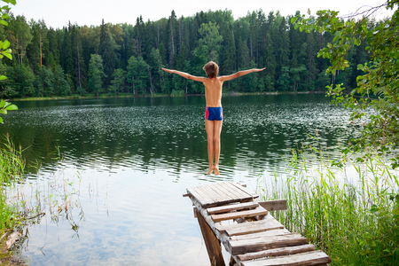 persona saltando: Niño salta de un muelle de madera en el agua en un bosque del verano