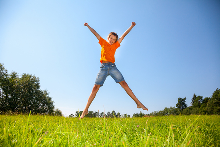 12 13: Boy enjoying summertime jumping on the sunny meadow in a summer forest