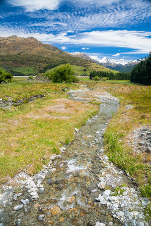 snow capped: New Zealands landscape with small stream or brook in foreground and snow capped mountains in background on a sunny summer day Stock Photo