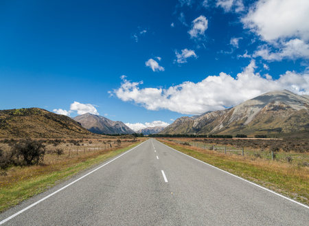 new direction: Straight road through valley in New Zealand with mountain range in background