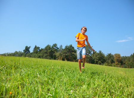 13: Boy enjoying summertime running through a sunny meadow in a summer forest Stock Photo