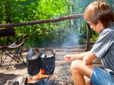 Young boy cooking camp food in cauldron on open fire Stock Photo