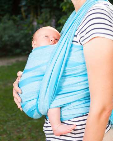 0 6 months: Young mother carrying her little baby girl in blue sling
