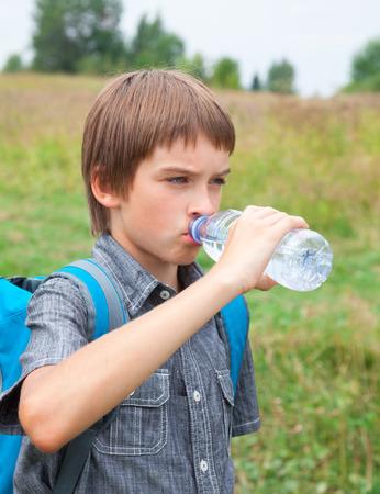 still water: Boy drinking still water from pet bottle outdoors