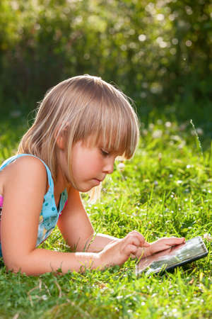 assiduous: Little girl usng a touch pad in a summer garden